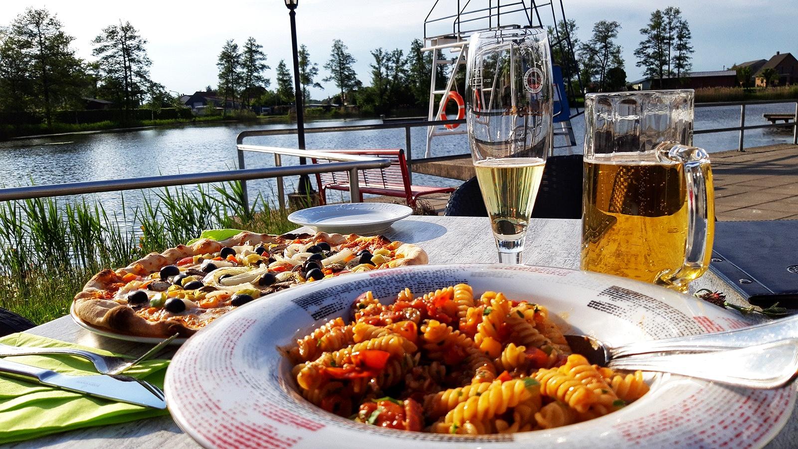 Pizza und Pasta auf einem Terrassentisch am See