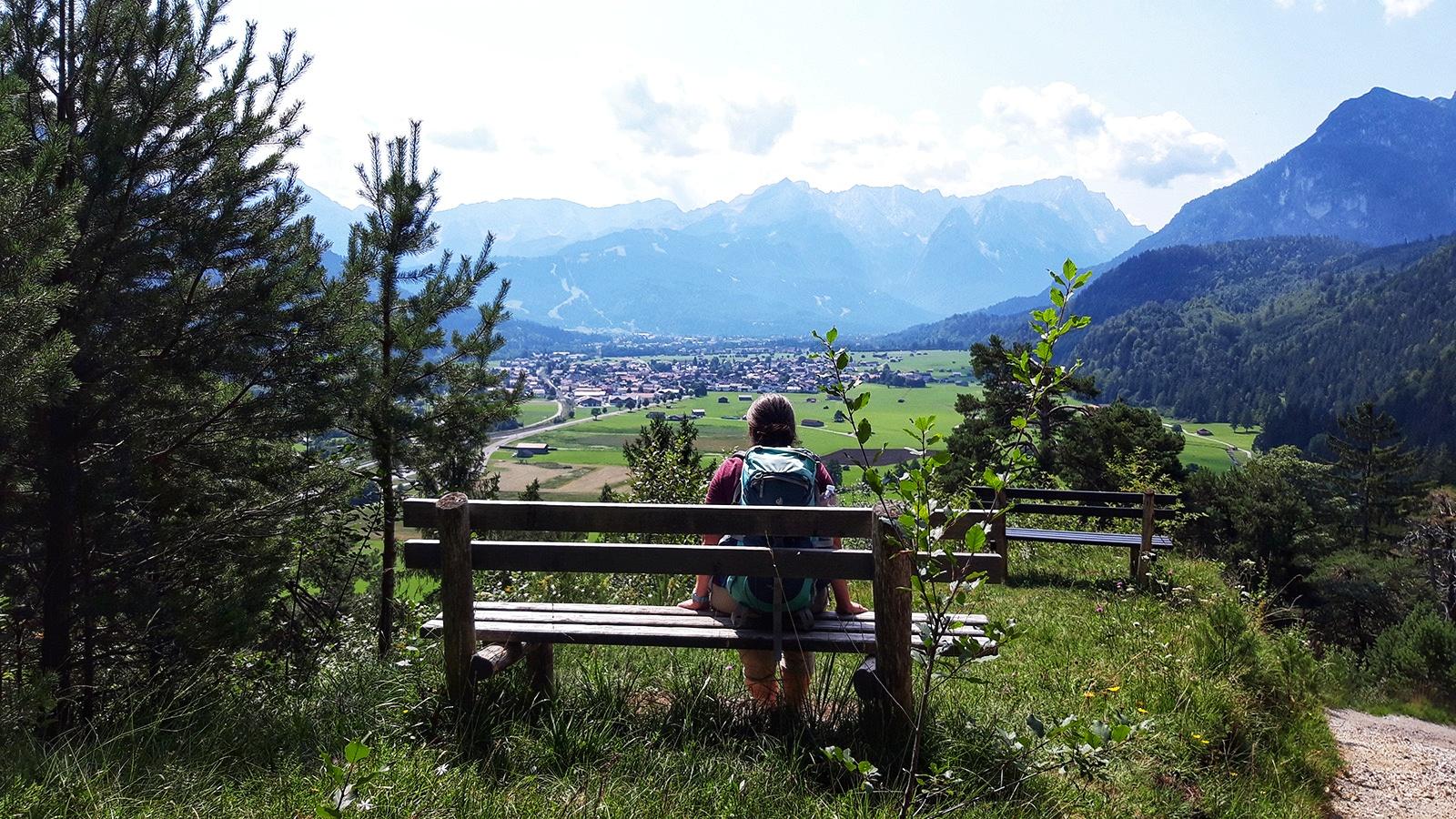 Wanderin pausiert auf einer Bank mit Aussichts in Tal und auf Berge