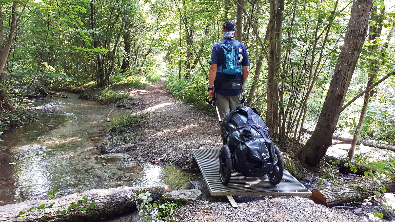 Wanderer mit Pilgerwagen überquert einen Bach auf einem Steg