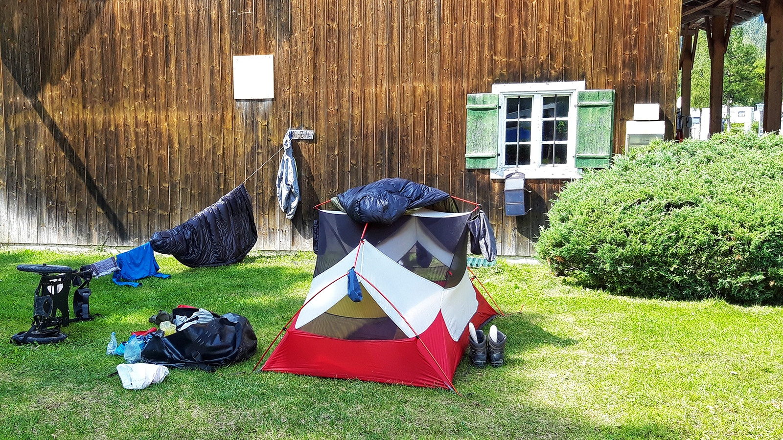 Zelt und Campingausrüstung vor einer Holzhütte
