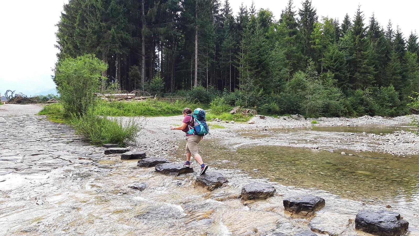 Wanderin nutzt Felsen, um einen Bach zu überqueren