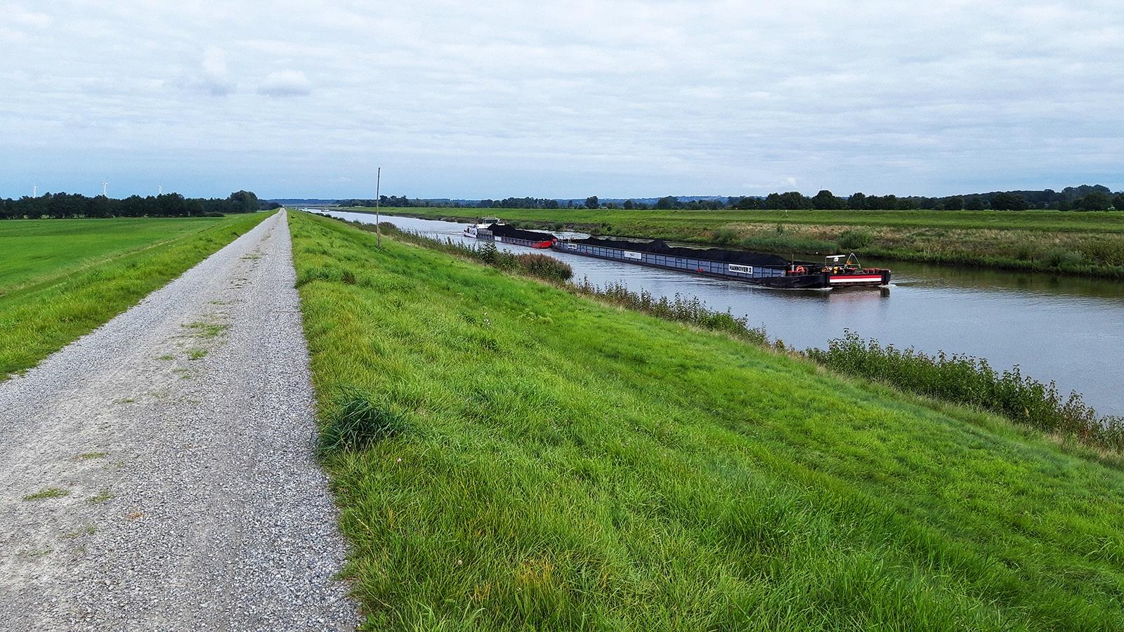 Schotterweg am Elbe-Seitenkanal mit Binnenschiff